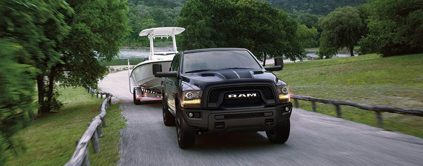 A black 2019 used Ram 1500 Classic is towing a boat away from a lake.