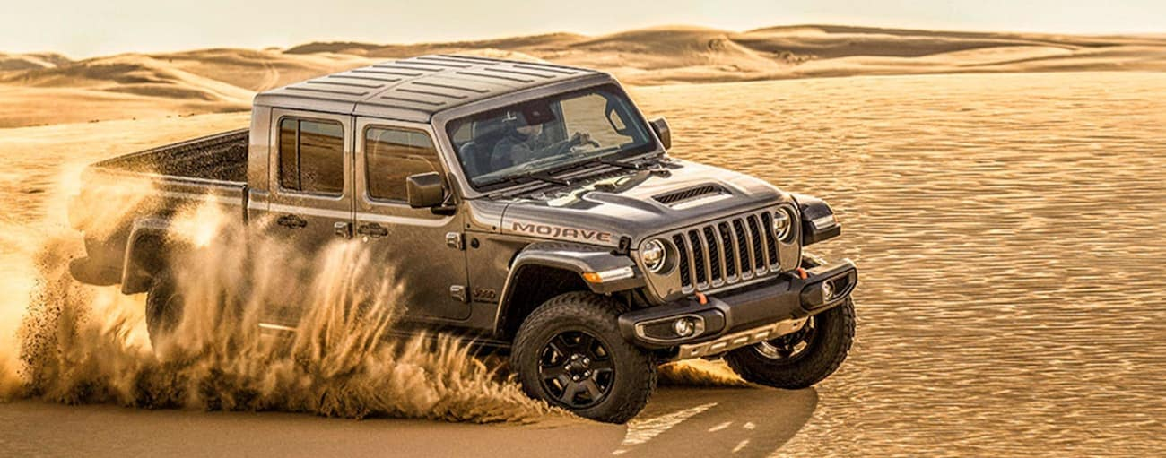 A grey 2021 Jeep Gladiator Mojave is off-roading in sand.