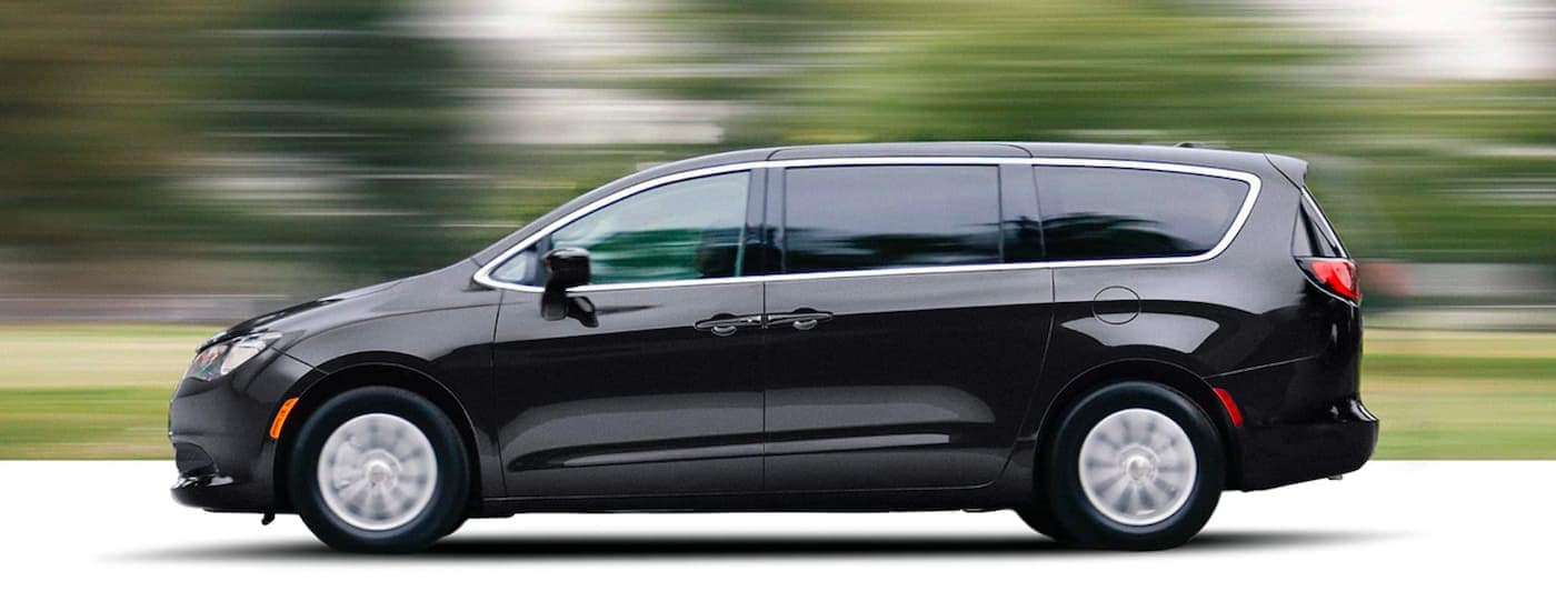 A black 2021 Chrysler Voyager is shown from the side speeding past blurred trees.