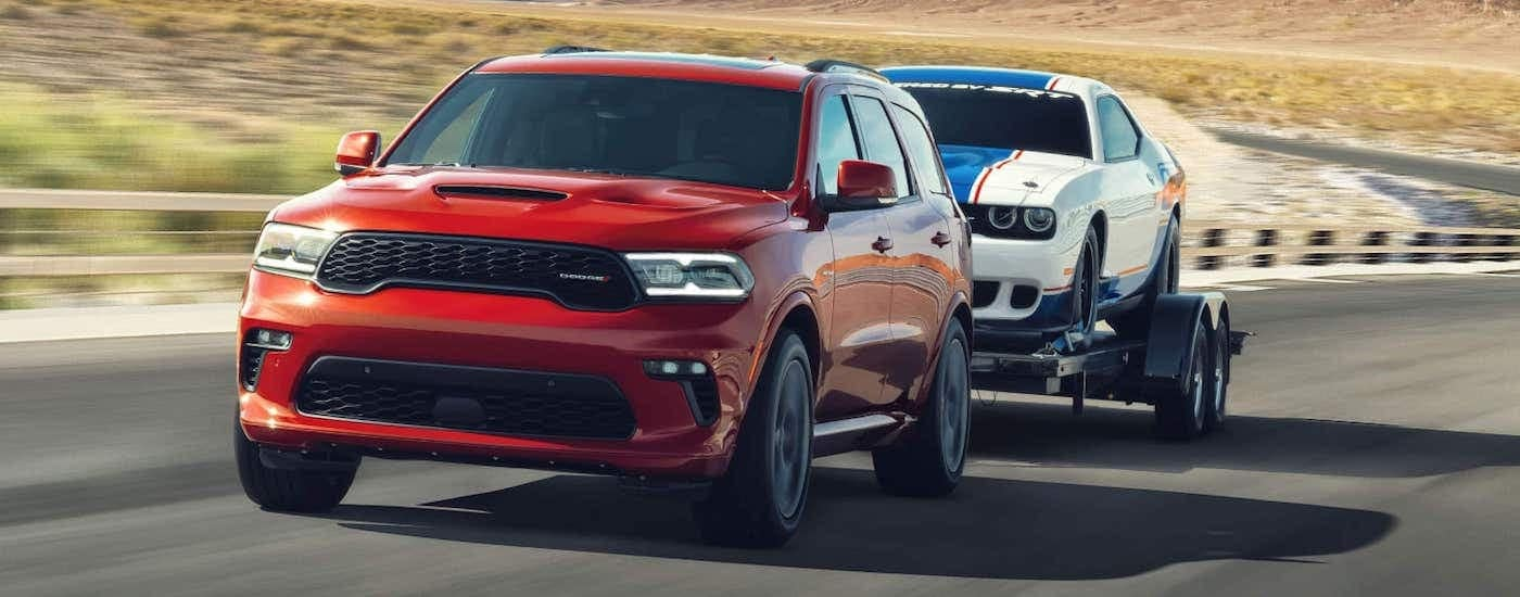 A red 2021 Dodge Durango is towing a white Dodge Challenger down the road on a trailer.