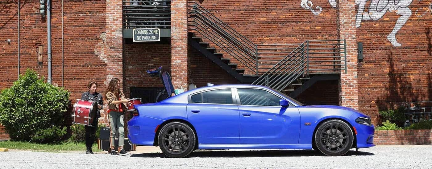 A blue 2019 Dodge Charger is shown from the side with drums being loaded into the trunk.