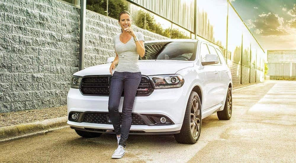 A white 2019 Dodge Durango is shown with a woman leaning against the grill after leaving a used Dodge dealer in Lexington.