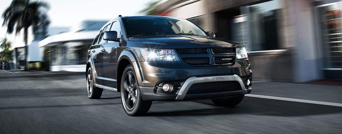 A black 2020 Dodge Journey is driving past blurred buildings.