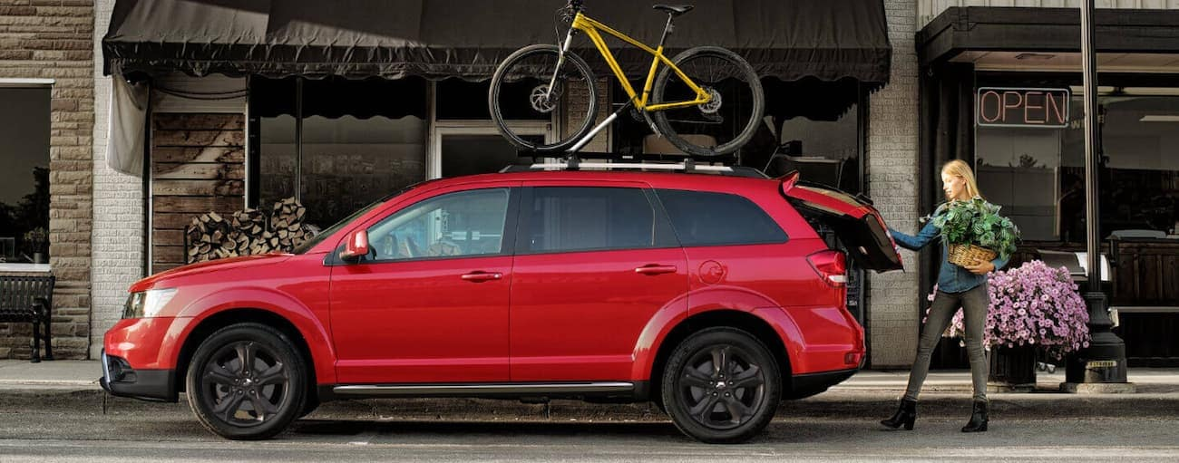 A woman is putting a plant in the back of a red 2020 Dodge Journey with a yellow bike on the roof.