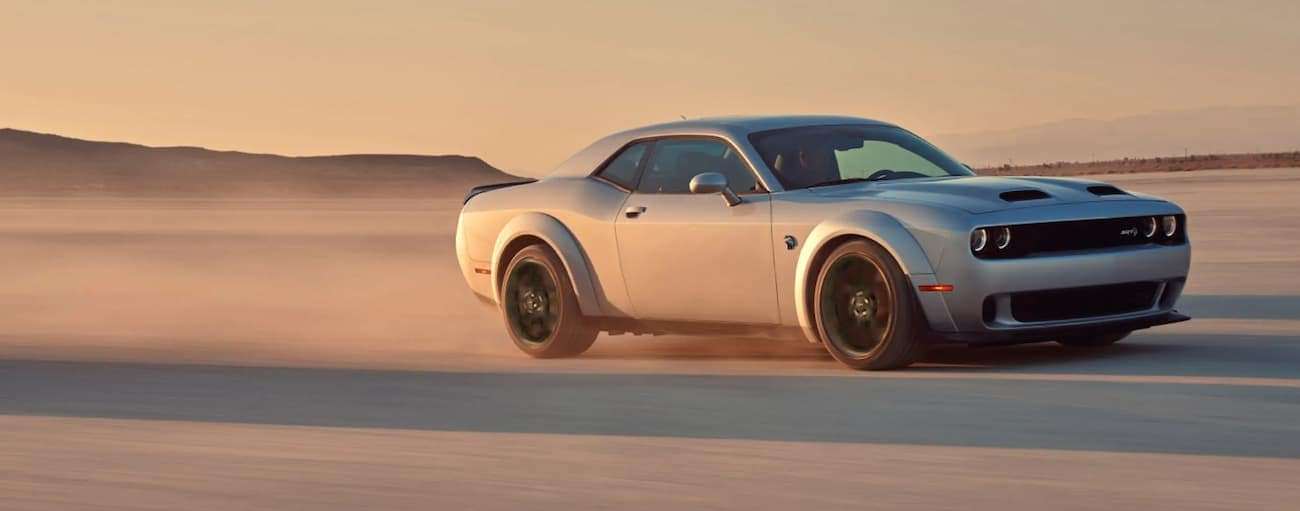 A silver 2021 Dodge Challenger is driving fast in a desert at sunset.
