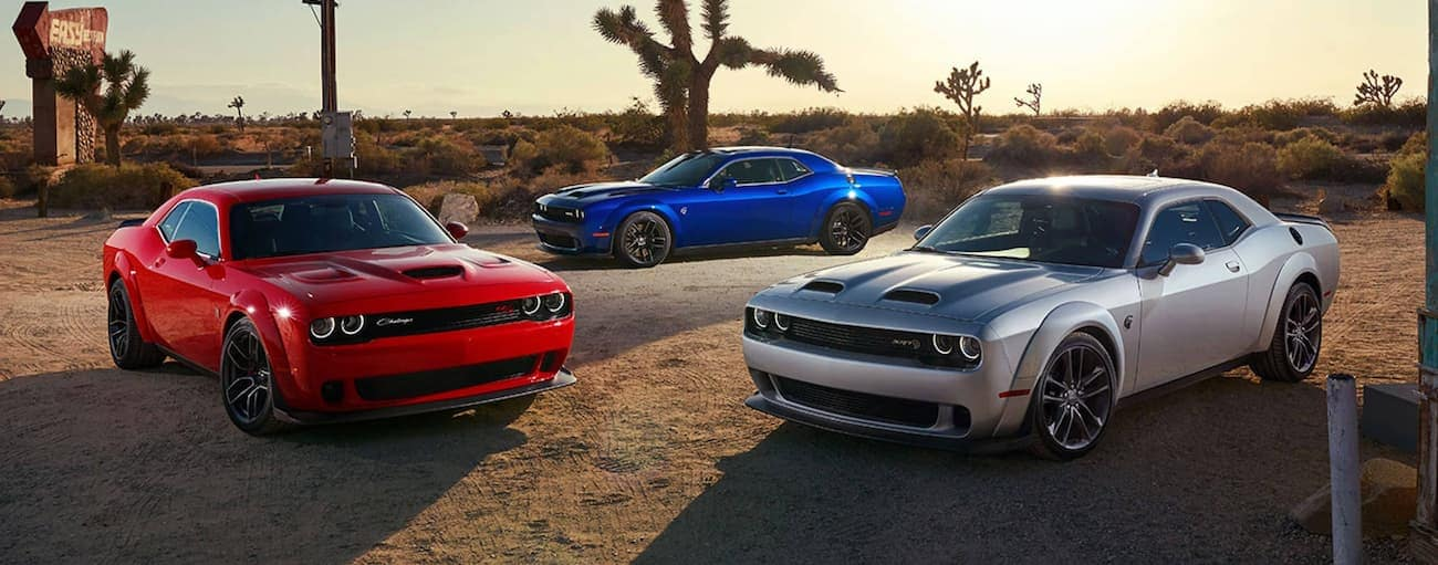 A red, a blue, and a silver 2021 Dodge Challenger are parked in the desert.