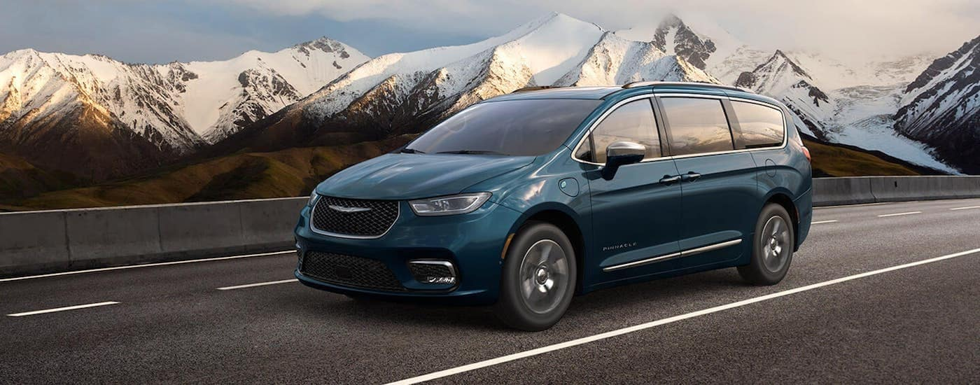 A blue 2021 Chrysler Pacifica is driving down the highway with distant snow covered mountains in the background.