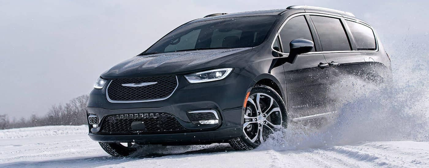 A black 2021 Chrysler Pacifica is shown kicking up snow in an empty field.