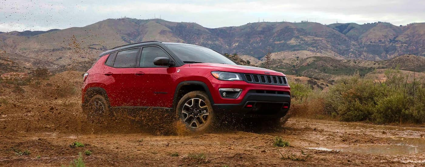A red 2021 Jeep Compass Trailhawk is shown from the side kicking up mud in a field.