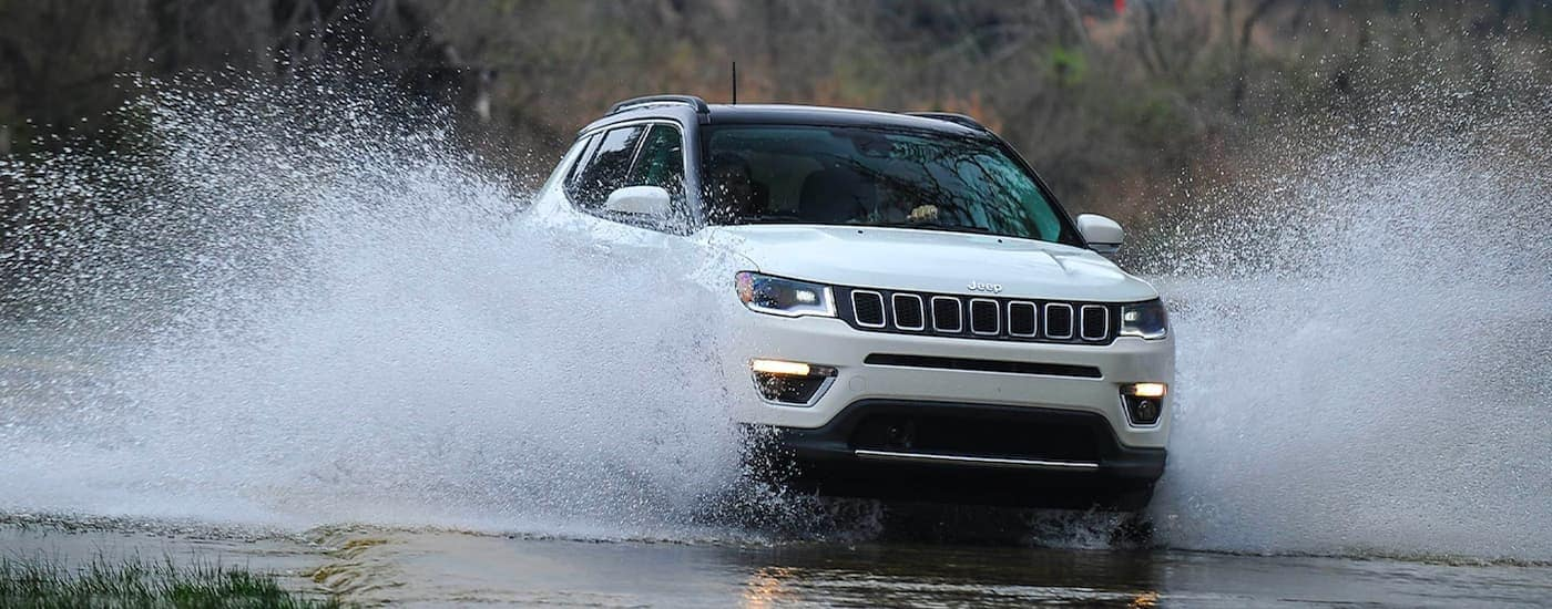 A white 2021 Jeep Compass is shown from the front driving through a river splashing up water.