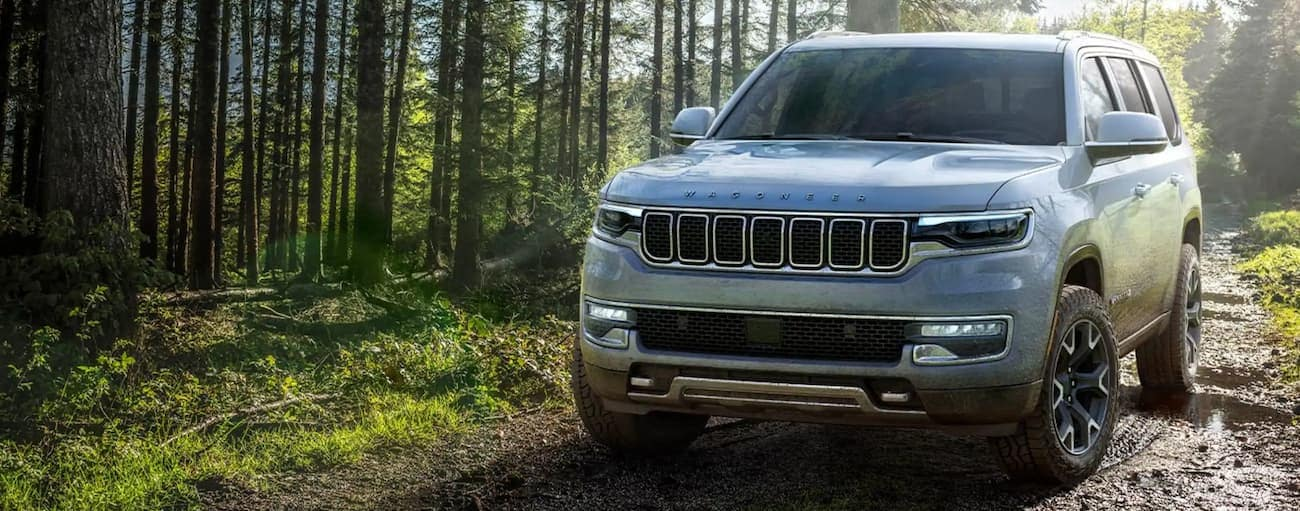 A grey 2022 Grand Wagoneer is on a muddy trail in the woods.