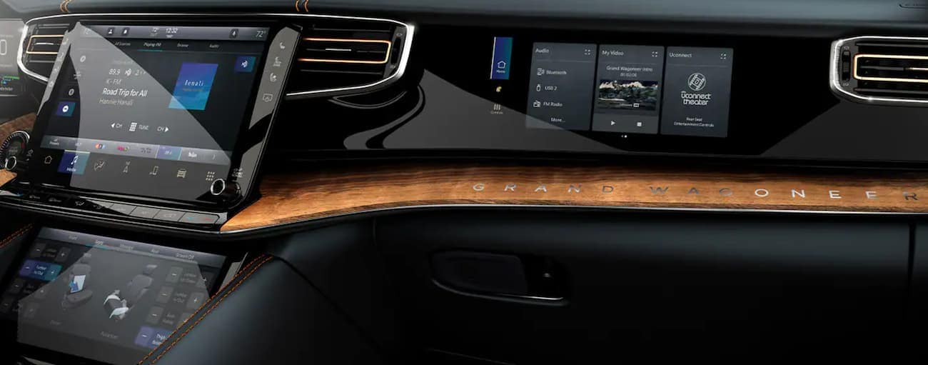 Multiple screens are shown on the black and wood dashboard in a 2022 Grand Wagoneer.