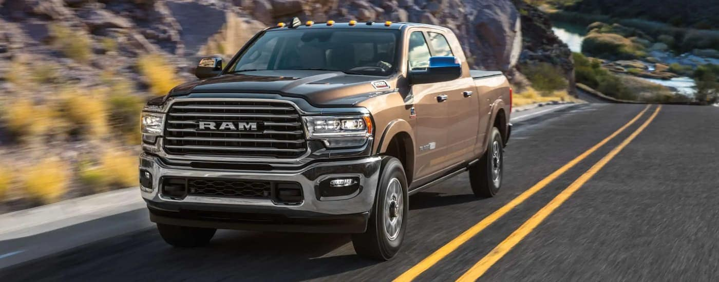A tan 2020 Ram 2500 Laramie Longhorn is driving uphill past rocky terrain.