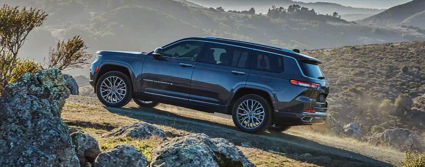 A gray 2021 Jeep Grand Cherokee L is shown from the side climbing a hill.