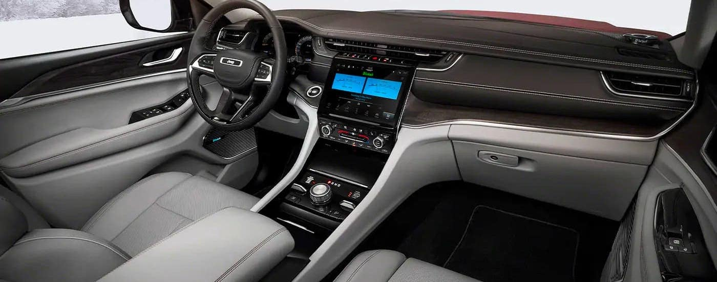 A black and gray interior, dashboard and steering wheel are shown in a 2021 Jeep Grand Cherokee L.