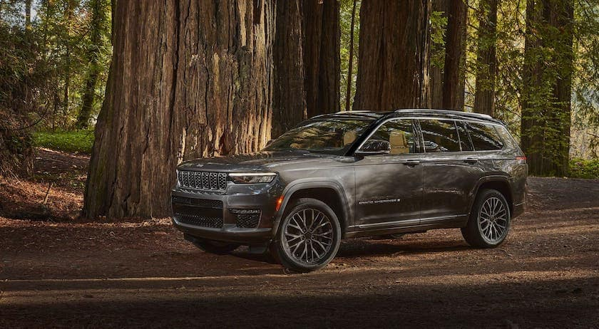 A gray 2021 Jeep Grand Cherokee L is parked beneath large evergreen trees.