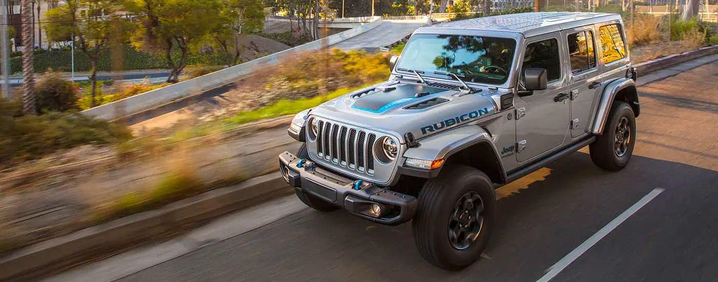A silver 2021 Jeep Wrangler 4xe Unlimited is shown from a high angle driving on a highway.