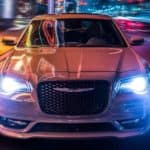 A white 2021 Chrysler 300 is shown from the front driving through the city after leaving a Lexington Chrysler dealership.