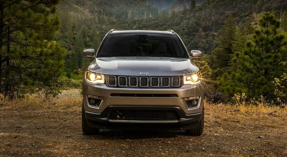 A gray 2017 used Jeep Compass is shown from the front parked in front of trees.