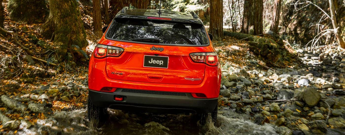 A red 2018 Jeep Compass Trailhawk is shown from the rear driving on a woodland trail.
