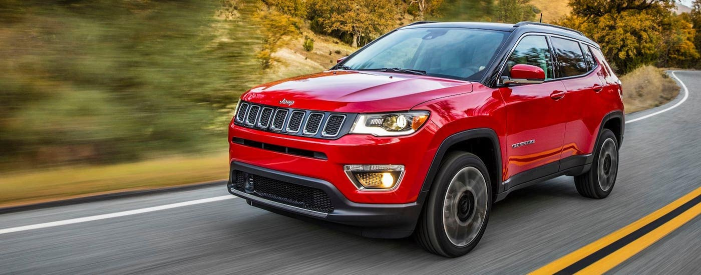 A red 2020 Jeep Compass is driving on a winding road.