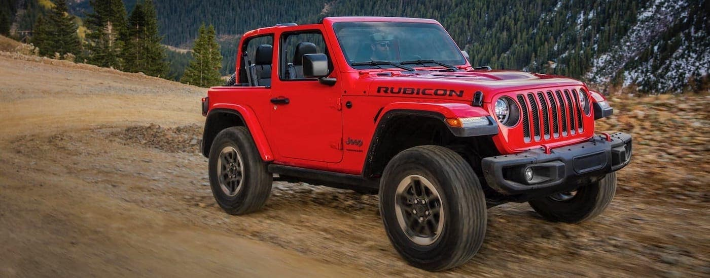 A red 2019 used Jeep Wrangler Rubicon is driving on a dirt trail in the mountains.