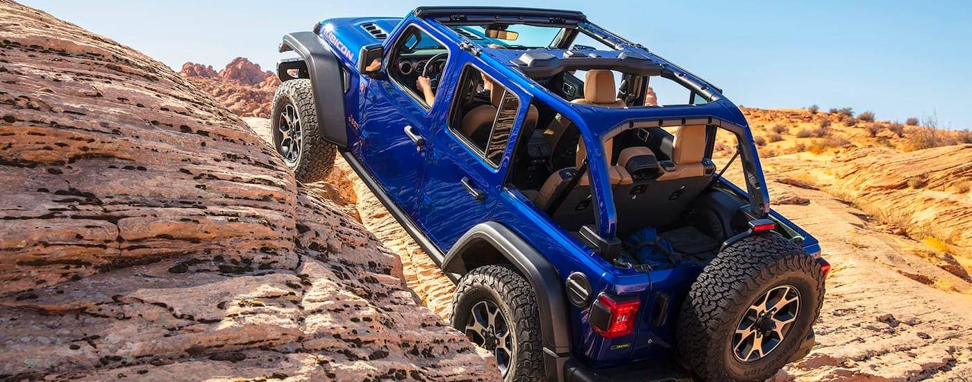 A blue 2020 Jeep Wrangler Unlimited Rubicon with no roof is climbing over rocks.