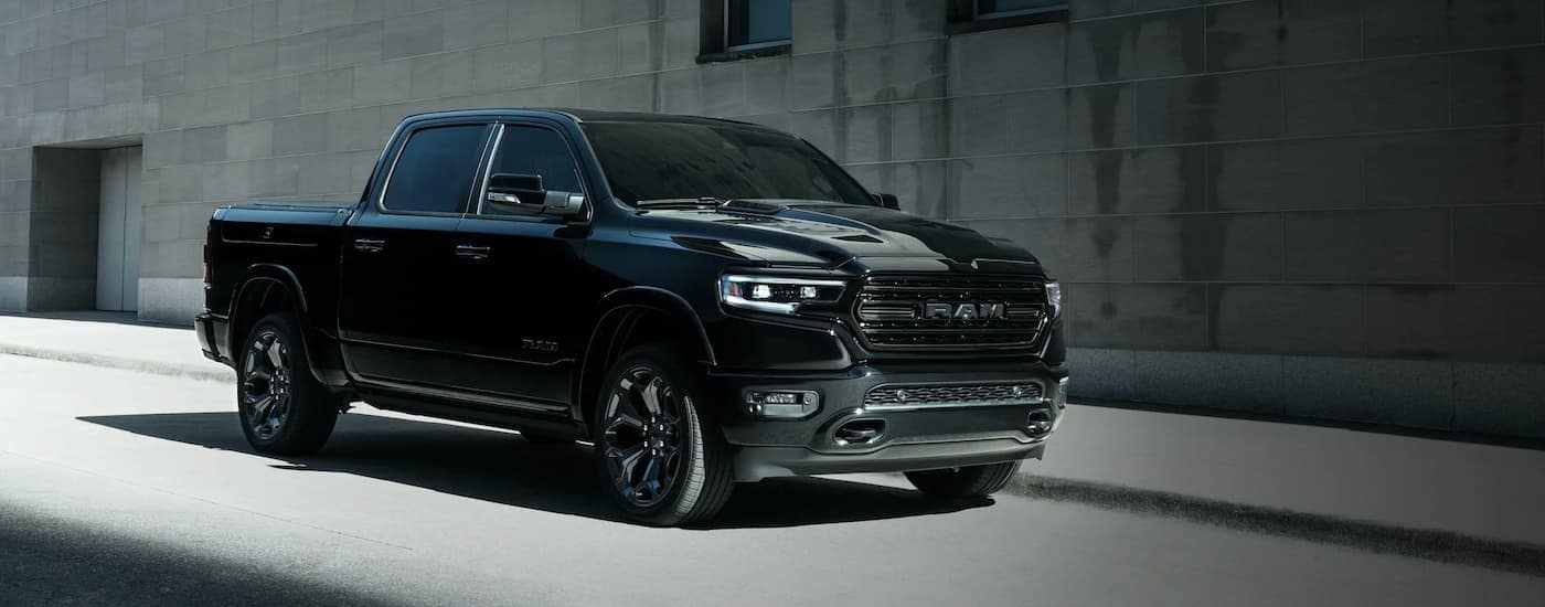 A black 2020 Ram 1500 is shown from the side parked by a concrete wall after leaving a used Ram dealership in KY