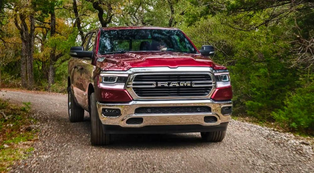 A red 2020 Ram 1500 is shown from the front driving through the woods.