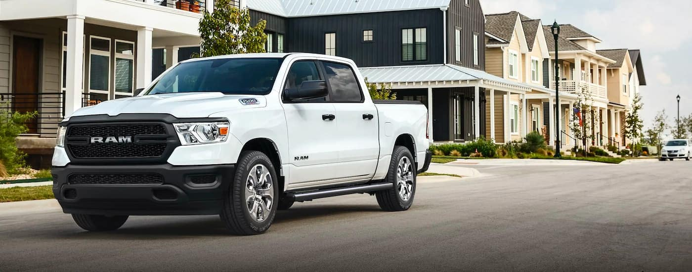 A white 2020 Ram 1500 is parked in a suburban neighborhood.