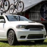 A white 2019 used Dodge Durango is parked outside of a barn.