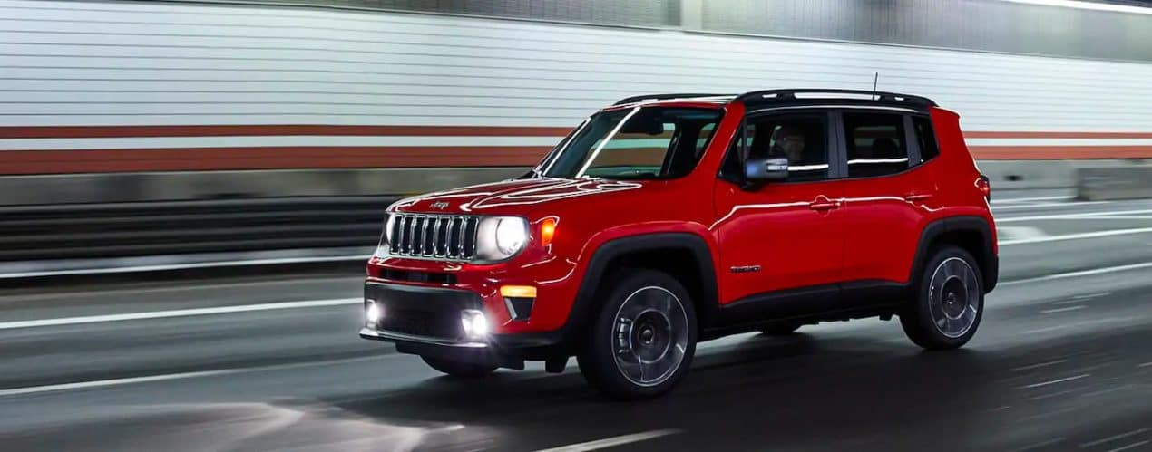 A red 2021 Jeep Renegade is shown driving through a tunnel.