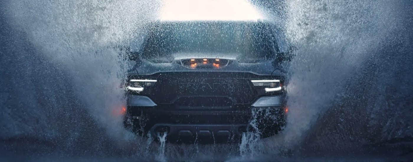 A grey 2021 Ram 1500 TRX is shown from the front splashing through water after leaving a Lexington Ram TRX dealer.