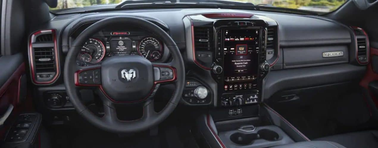 The interior of a black 2021 Ram 1500 shows the steering wheel and infotainment screen.