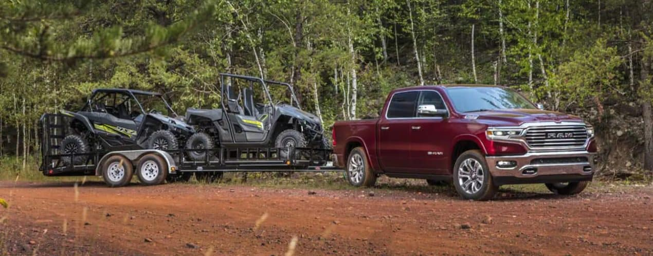 A red 2021 Ram 1500 is towing two side by sides in a field lined with trees.