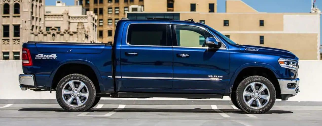 A blue 2021 Ram 1500 is shown from the side parked in a lot after leaving a Ram Truck Dealership in Lexington.