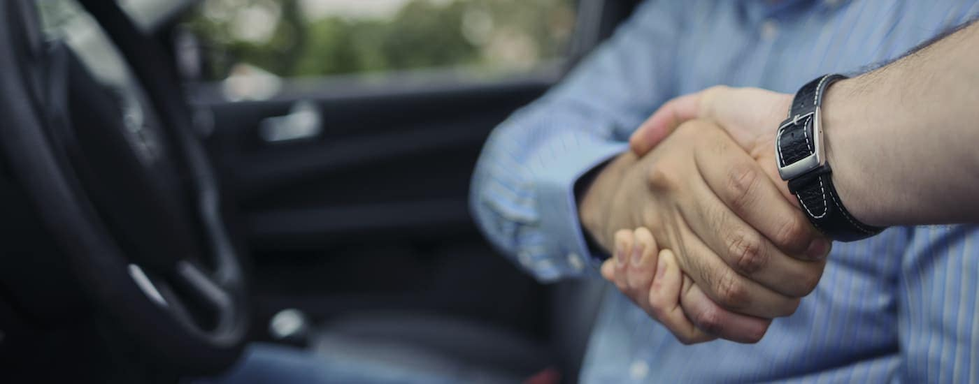 A man is sitting in the front seat of a used car and shaking someones hand at a Kentucky used car lot.