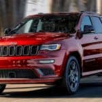 A red 2020 Jeep Grand Cherokee is shown driving through a city.