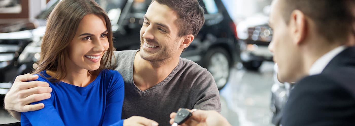 couple at dealership getting car keys