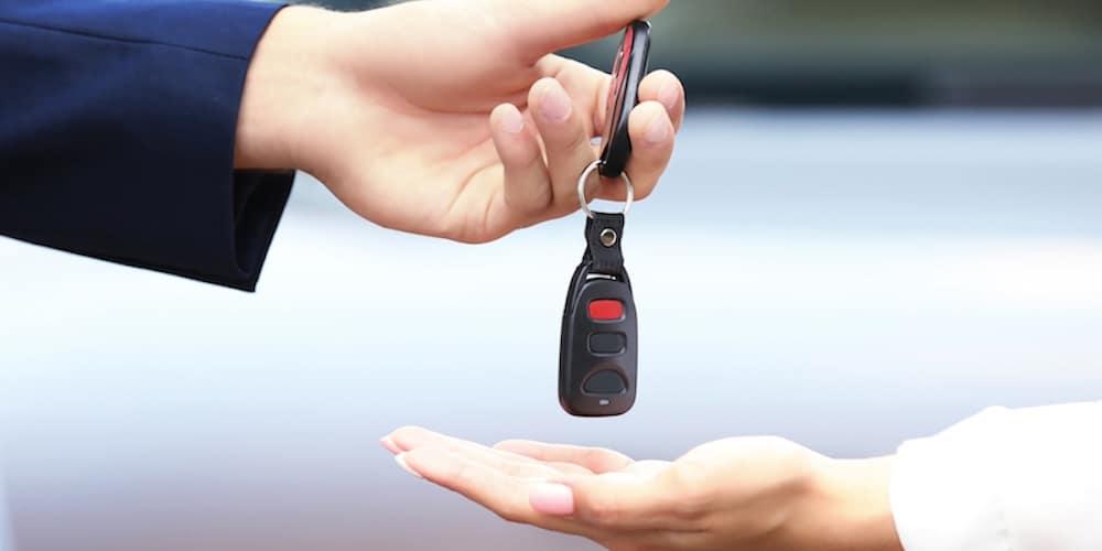 man handing woman keys to car