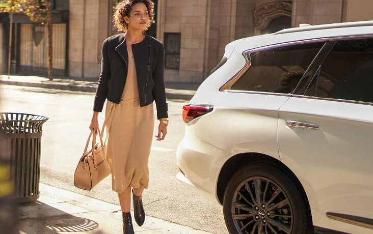 A woman walking past a 2021 INFINITI QX80
