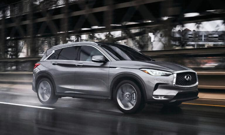2021 INFINITI QX50 driving on wet road in Chicago city