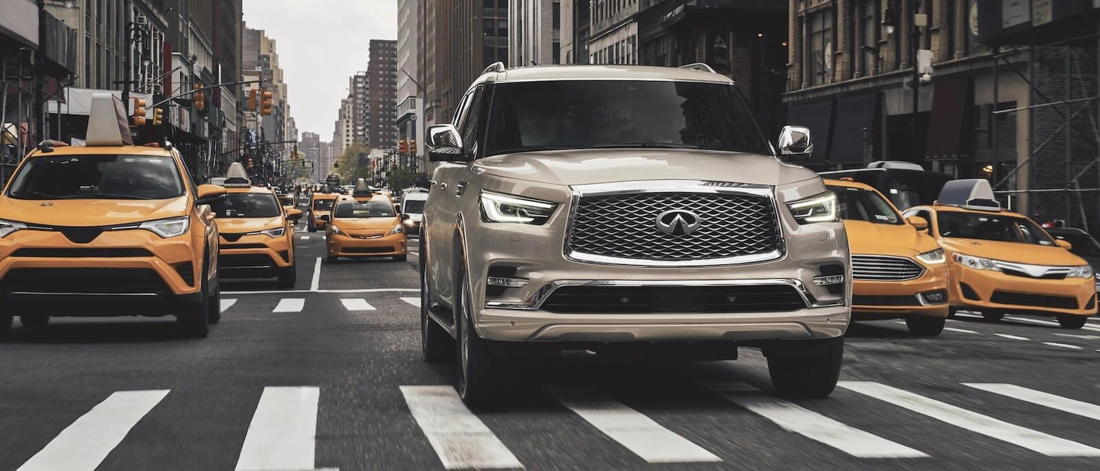 An INFINITI QX80 driving in a sea of cabs