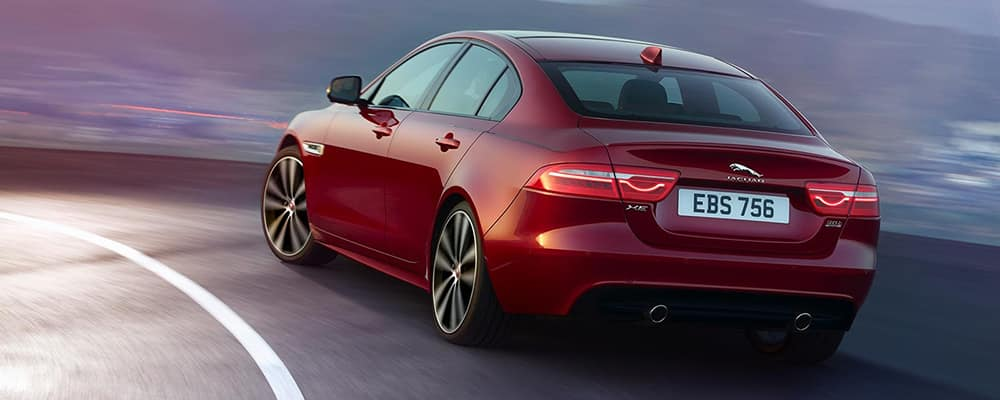 red 2020 jaguar xe driving on road