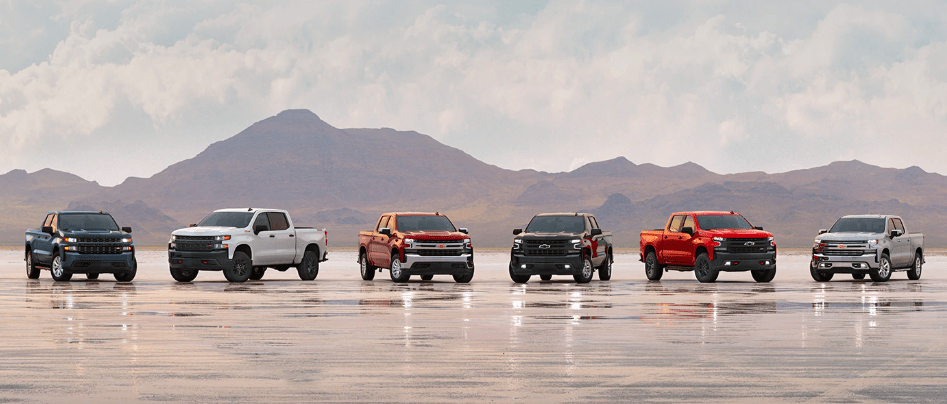 A row of 2019 Chevy Silverado Editions Parked in front of a Mountain