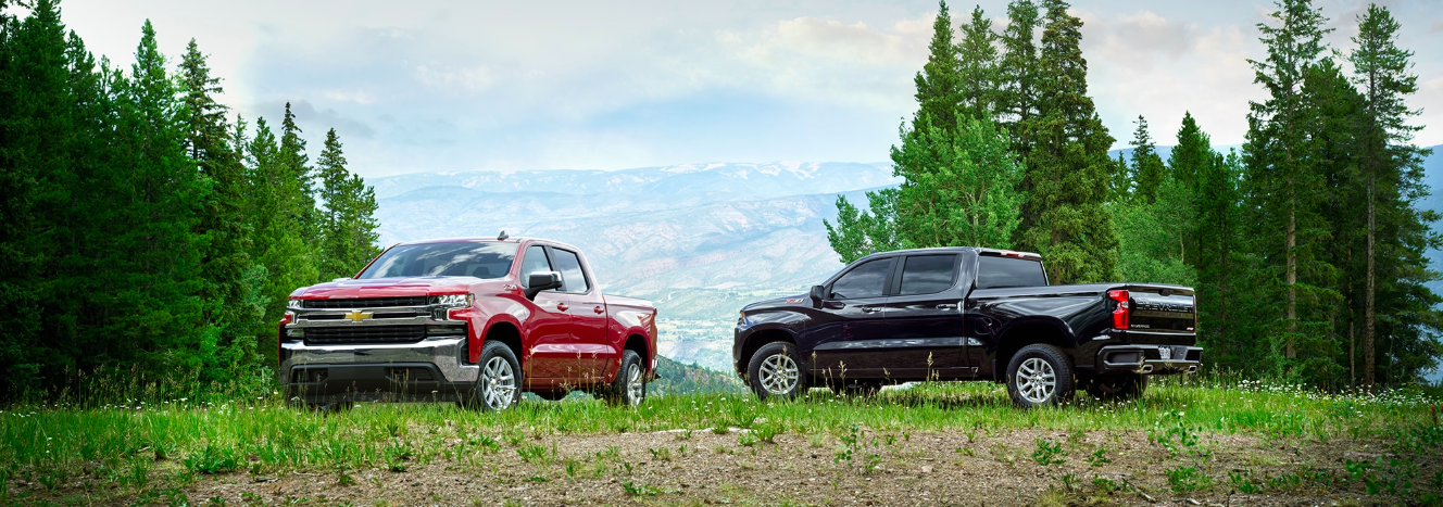 Two 2020 Chevrolet Silverado trucks parked side by side with a mountain in the background