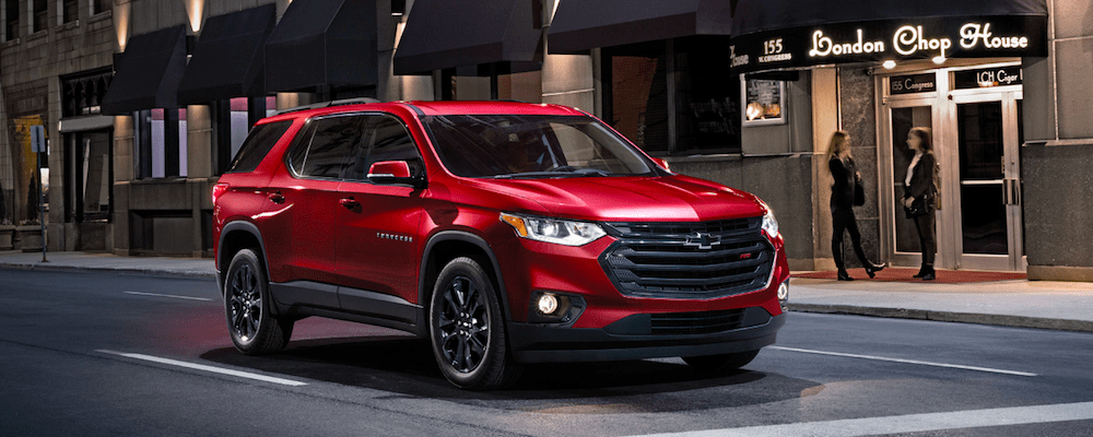 A 2020 Chevy Traverse driving on a city street at night