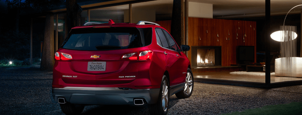 A 2020 Chevy Equinox parked outside of a new home