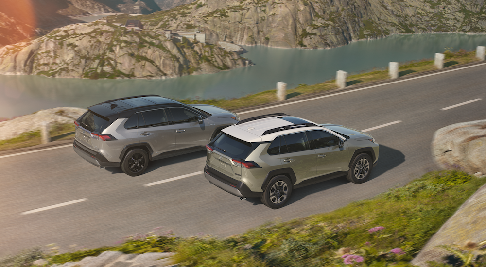 A silver and pearl 2019 Rav4 driving on road above river