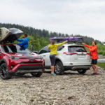 Red and white 2019 Toyota Rav4s with canoes next to river